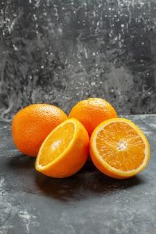 Widok z przodu całych i pokrojonych naturalnych organicznych świeżych pomarańczy ułożonych w dwóch rzędach na ciemnym tle