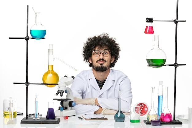 Widok z przodu chemik w stroju medycznym, siedzący przed stołem z roztworami na jasnobiałej przestrzeni