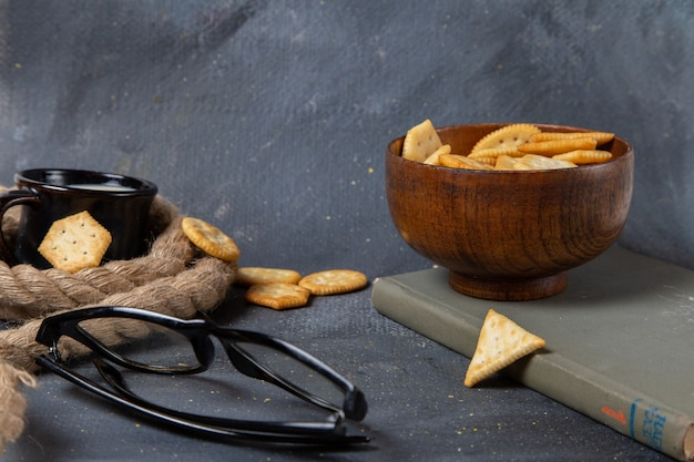 Widok z przodu chipsów i krakersów z sznurem mlekiem i okularami przeciwsłonecznymi na szarej powierzchni