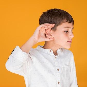 Widok z przodu chłopca próbuje czegoś słuchać