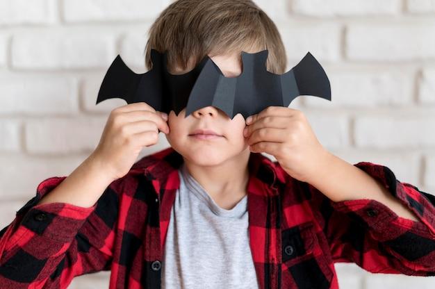 Widok z przodu chłopca z papierowym nietoperzem