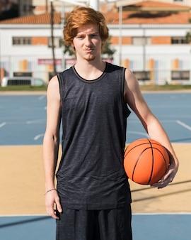 Widok z przodu chłopca z piłką do koszykówki