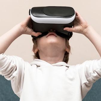 Widok z przodu chłopca za pomocą zestawu słuchawkowego wirtualnej rzeczywistości
