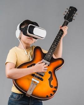 Widok z przodu chłopiec gra na gitarze podczas korzystania z zestawu słuchawkowego rzeczywistości wirtualnej