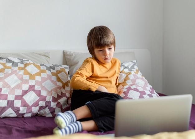 Widok z przodu chłopiec siedzi w łóżku i nauki