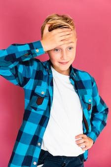 Widok z przodu chłopiec stojący z jedną ręką na czole
