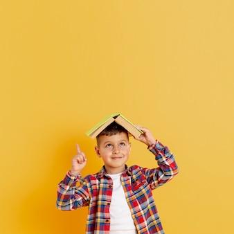 Widok z przodu chłopiec trzyma książkę na głowie