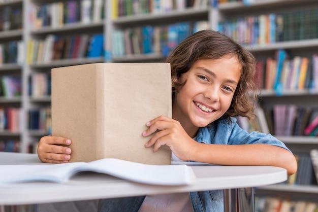 Widok z przodu chłopiec trzyma otwartą książkę