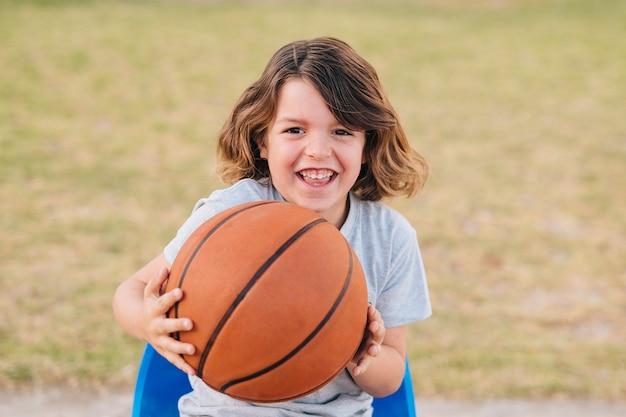 Widok z przodu chłopiec trzyma piłkę
