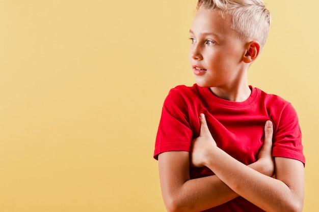 Widok z przodu chłopiec z ramionami pod pachami, patrząc od hotelu