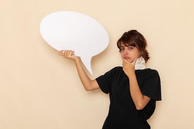 Widok z przodu chora młoda kobieta czuje się chora i trzyma ogromny biały znak na jasnobiałej powierzchni