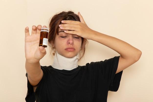 Widok z przodu chora młoda kobieta źle się czuje i trzyma pigułki na jasnobiałej powierzchni
