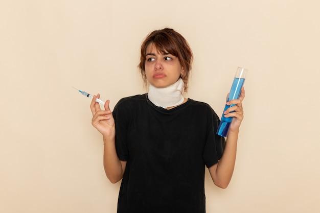Widok z przodu chora młoda kobieta źle się czuje i trzyma zastrzyk na białej powierzchni