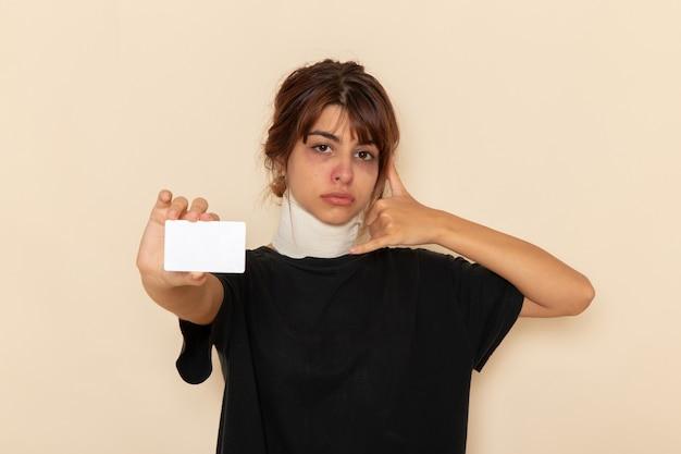 Widok z przodu chora młoda kobieta źle się czuje trzymając białą kartę na białej powierzchni