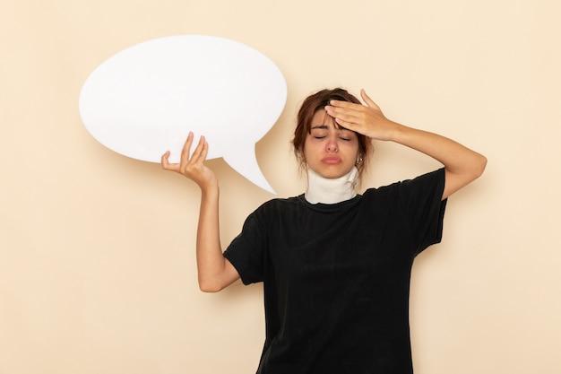Widok z przodu chora młoda kobieta źle się czuje, trzymając ogromny biały znak na białej powierzchni