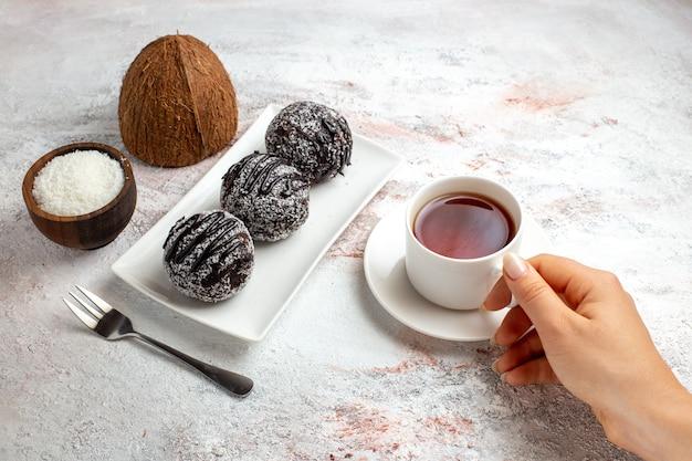 Widok z przodu ciasta czekoladowe z filiżanką herbaty na białym biurku ciasto czekoladowe herbatniki cukier słodkie ciasteczka