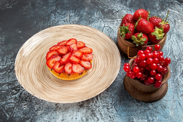 Widok z przodu ciasta owocowego ze świeżymi truskawkami na ciemnej powierzchni