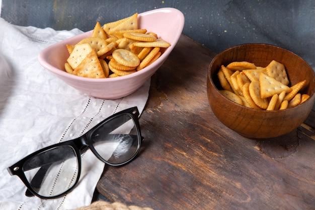 Widok z przodu ciastek i krakersów wewnątrz różowego talerza z okularami przeciwsłonecznymi na drewnianym biurku