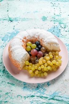 Widok z przodu ciasto cukrowe w proszku pokrojone pyszne ze świeżymi winogronami na jasnoniebieskiej powierzchni ciasto owocowe piec cukier słodkie ciasto biszkoptowe