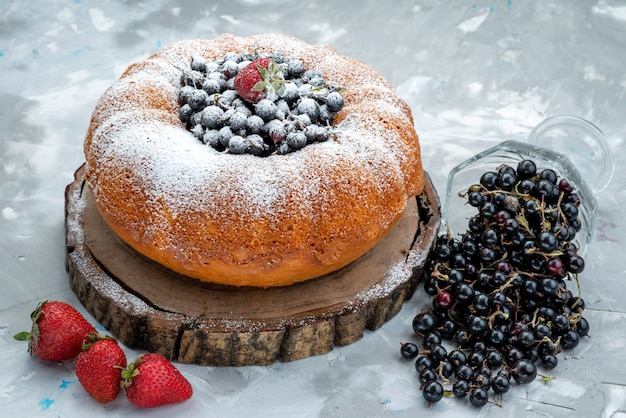 Widok z przodu ciasto owocowe pyszne i okrągłe uformowane ze świeżym niebieskim, jagodami na jasnym, słodkim cukrze ciastka herbatnikowe