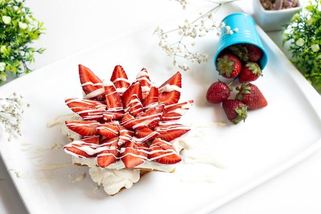 Widok z przodu ciasto truskawkowe z kremem i pokrojonymi czerwonymi truskawkami wraz ze świeżymi całymi truskawkami wewnątrz białego biurka z cukrem jagodowym