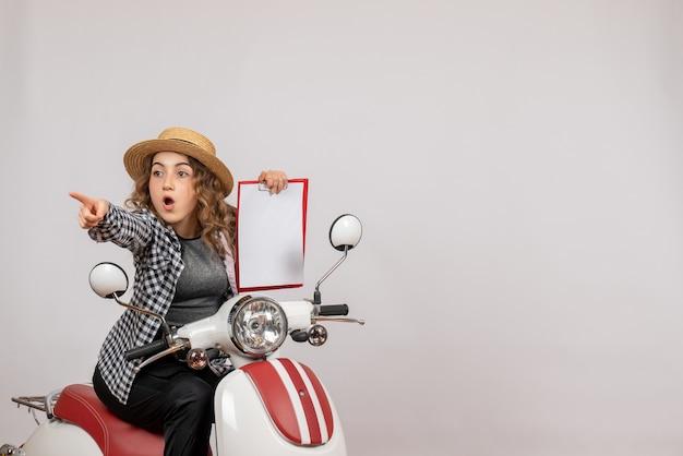 Widok z przodu ciekawa młoda dziewczyna na motorowerze trzymając schowek na szarej ścianie