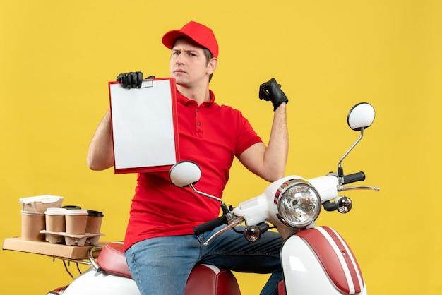 Widok z przodu ciekawy kurier ubrany w czerwoną bluzkę i kapeluszowe rękawiczki w masce medycznej dostarczania zamówienia siedzącego na skuterze dokument posiadania