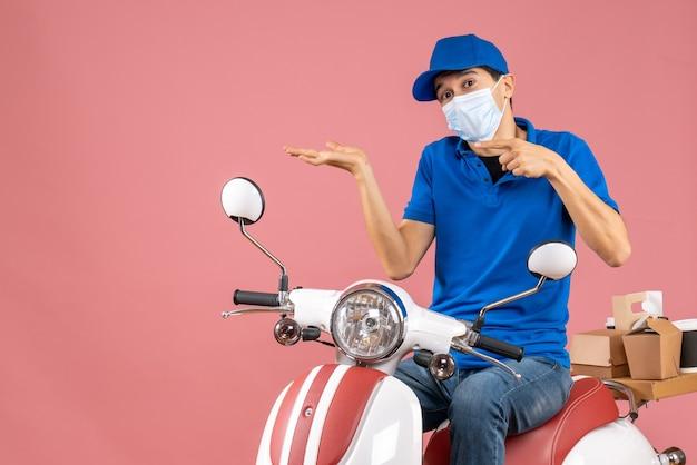 Widok z przodu ciekawy kurier w masce medycznej w kapeluszu siedzi na skuterze na pastelowym tle brzoskwini