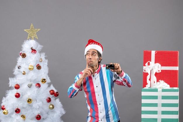 Widok z przodu ciekawy mężczyzna z kartą kredytową kładąc dłoń na policzku stojący w pobliżu różnych prezentów