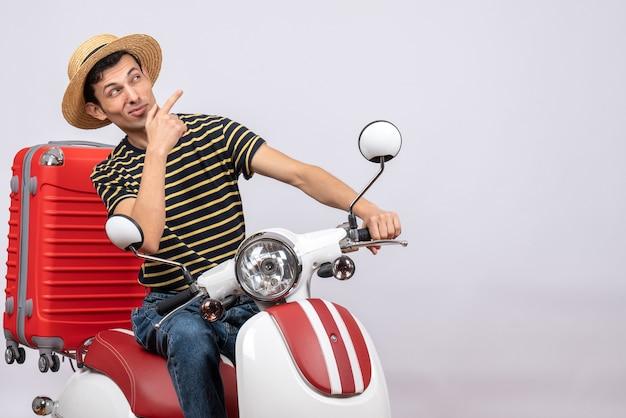 Widok z przodu ciekawy młody chłopak z słomkowym kapeluszem na motorowerze patrząc na coś