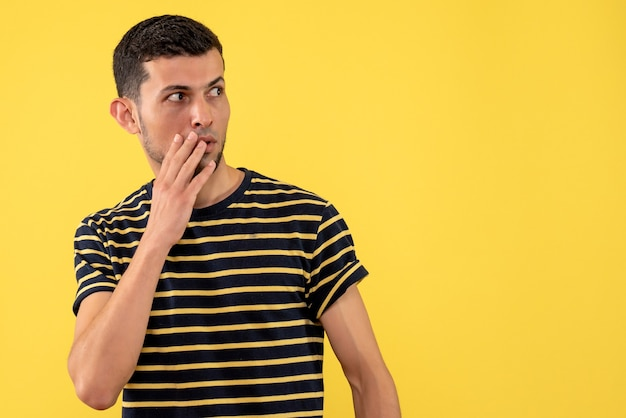 Widok z przodu ciekawy młody człowiek w czarno-białej koszulce w paski żółte tło na białym tle wolne miejsce