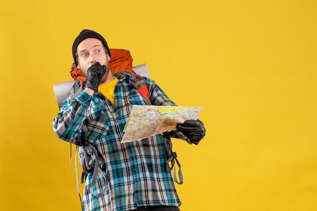 Widok z przodu ciekawy młody turysta ze skórzanymi rękawiczkami i plecakiem trzymając mapę