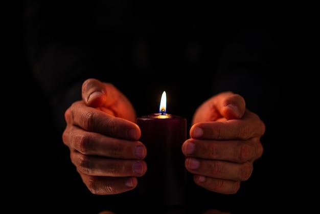Widok z przodu ciemnej świecy z mężczyzną na ciemnej powierzchni