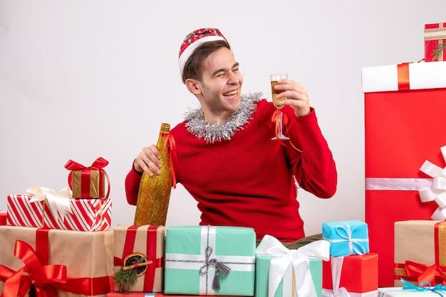 Widok z przodu cieszył się młody człowiek siedzący wokół świątecznych prezentów