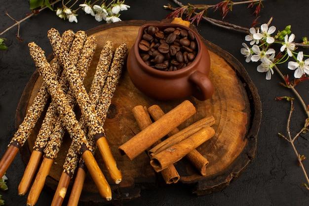 Widok z przodu cukierków laski wraz z kawą i cynamonem na brązowym biurku i ciemności