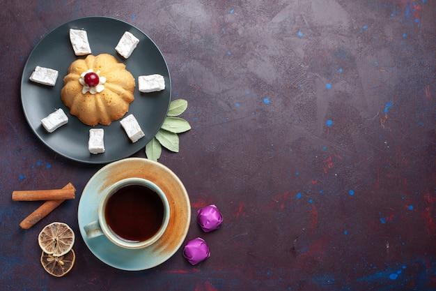 Widok z przodu cukierków w proszku z cukrem pyszny nugat z ciastem i herbatą wewnątrz talerza na ciemnej powierzchni