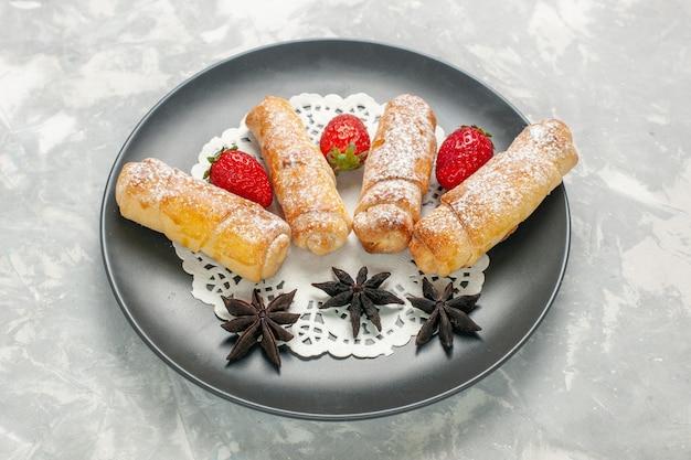 Widok z przodu cukrowych bułeczek w proszku z truskawkami na białym biurku