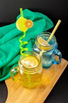 Widok z przodu cytryny koktajl świeży chłodny napój wewnątrz szklanych kubków pokrojone w plasterki i całe cytryny słomki na ciemnym tle koktajl owocowy