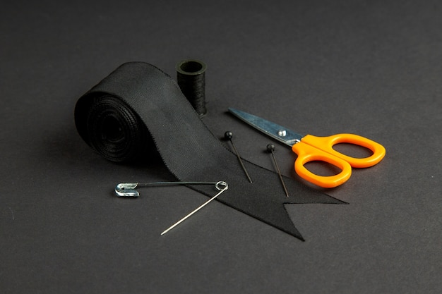 Widok z przodu czarna kokarda ze szpilką i nożyczkami na ciemnej powierzchni ciemność szycie na drutach w kolorze zdjęcie