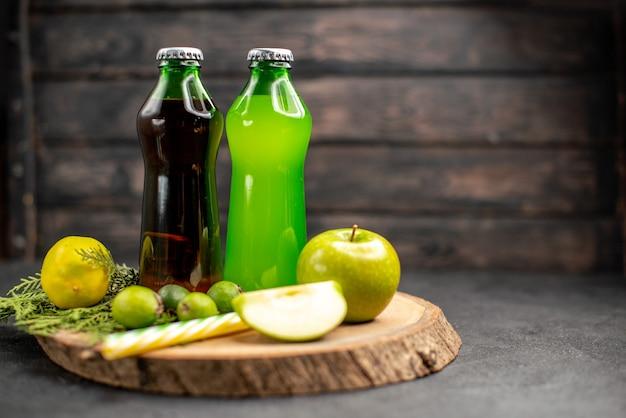 Widok z przodu czarna zielona lemoniada w butelkach jabłko cytryna pipety feijoas na desce drewnianej