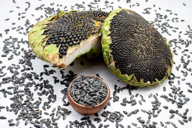 Widok z przodu czarne pestki słonecznika świeże i smaczne wnętrze ziaren słonecznika w łupinach