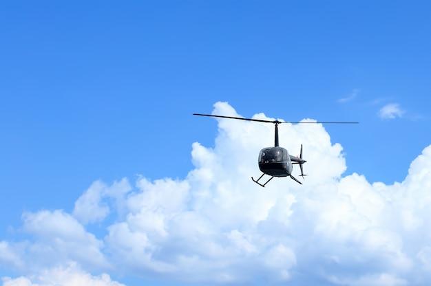 Widok z przodu czarnego helikoptera na niebieskim niebie