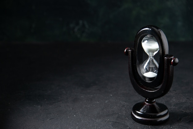 Widok z przodu czarnej klepsydry na ciemnej powierzchni
