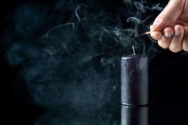 Widok z przodu czarnej świecy zapalającej się przez mężczyznę na ciemnej powierzchni