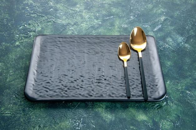 Widok z przodu czarny talerz ze złotymi łyżkami na ciemnoniebieskim tle
