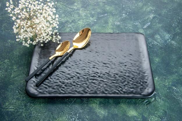 Widok z przodu czarny talerz ze złotymi łyżkami na ciemnym tle