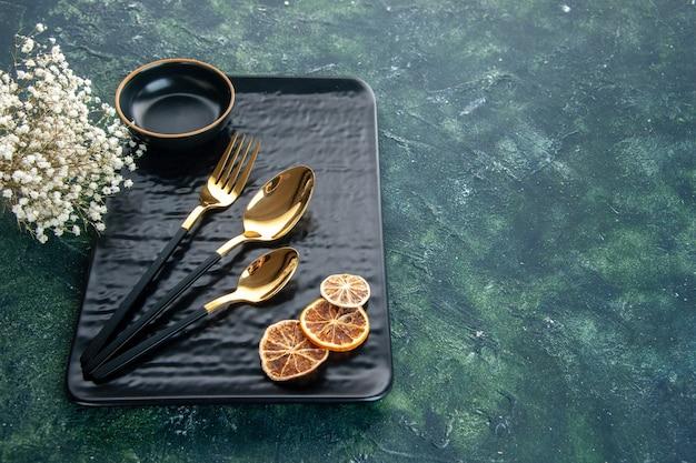 Widok z przodu czarny talerz ze złotymi sztućcami na ciemnym tle