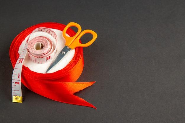 Widok z przodu czerwona kokarda z nożyczkami i centymetrami na ciemnym tle