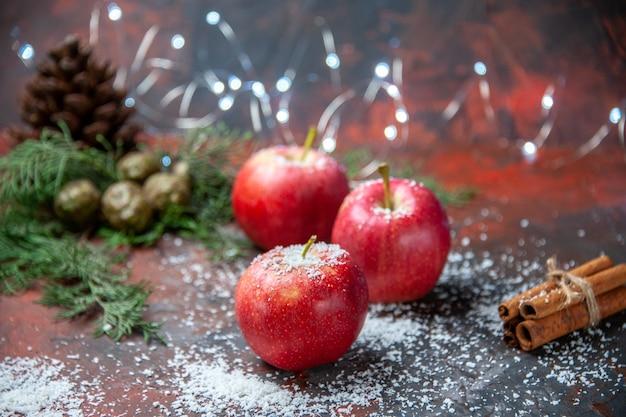 Widok z przodu czerwone jabłka laski cynamonu proszek kokosowy na ciemnym