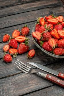Widok z przodu czerwone truskawki pokrojone i całe owoce na ciemnym drewnianym rustykalnym biurku letni kolor sok z drzewa jagoda dzika